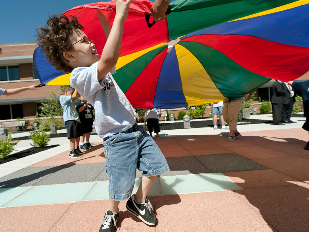Child playing with giant parachute